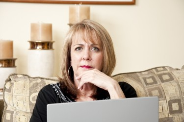 Mature woman sitting on her couch using her laptop computer